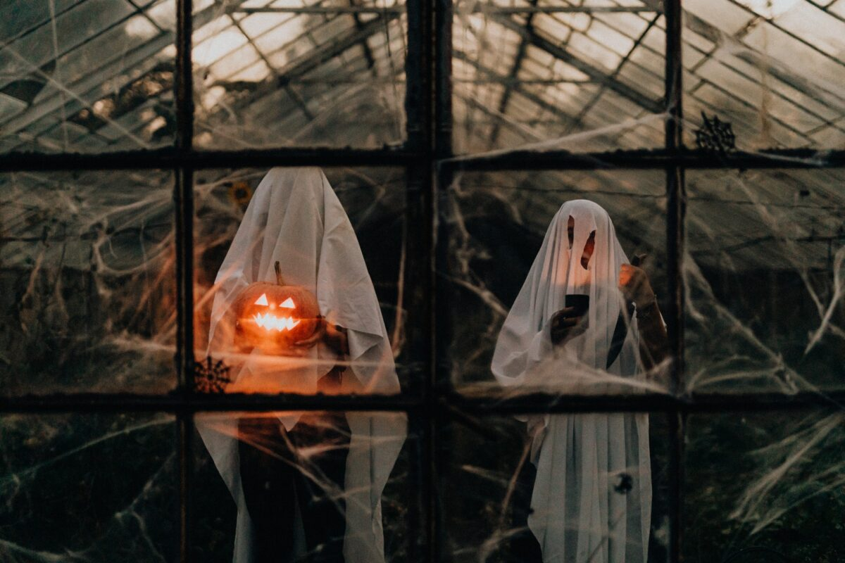 A pair of Ghosts are in a greenhouse, holding a lit Jack O'Lantern